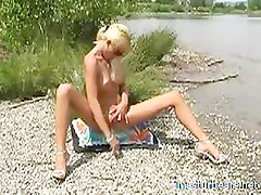 Frieda toying and cumming on a lake beach